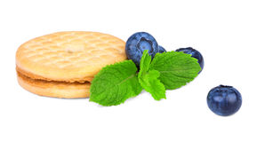 A cereal biscuit with blueberries and mint leaves. A light sweet snack isolated on a white background. A sweet and organic cookie. Stock Photography