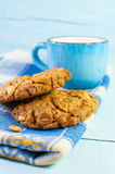 Cereal biscuits and cup of milk on a blue wooden surface. Stock Photos