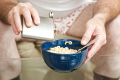 Cereal with Booze. Alcoholic spiking his cereal with vodka from a flask.  Shallow depth of field with focus on the pouring alcohol Royalty Free Stock Images