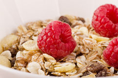 Cereal breakfast with muesli, nuts, and fresh raspberries. Healthy breakfast. Cereal breakfast with muesli, nuts, and fresh raspberries in a white bowl, close-up Stock Images