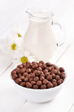 Cereal chocolate balls and jug of milk Stock Photo
