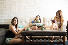 Cereal and coffee for breakfast. Beautiful Latin female friends wearing pajamas and having some breakfast in the morning at home Royalty Free Stock Image