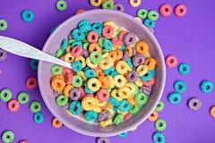 Cereal colorido na bacia em um fundo roxo Fotografia de Stock