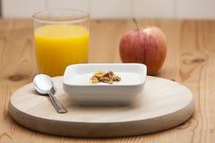 Cereal con el yogur y el zumo de naranja con la manzana Fotos de archivo libres de regalías