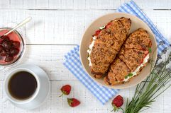 Cereal croissants with cream cheese and fresh strawberries, cup of tea and jam stock image