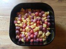 Cereal da manhã em uma bacia preta com leite Imagem de Stock Royalty Free