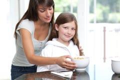 Cereal de desayuno de la hija de la mama que introduce imagen de archivo