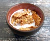 Cereal de desayuno del salvado de trigo con leche en cuenco de la arcilla Imagen de archivo libre de regalías