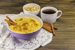 Cereal del maíz con los cacahuetes y el canela en un cuenco púrpura imagenes de archivo