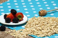Cereal e morangos, amoras-pretas em uns pires na tabela Foto de Stock