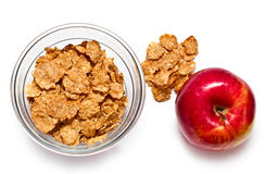 Cereal flakes and apple. Corn flakes in a glass bowl and apple on a white background Stock Photo