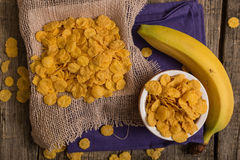 Cereal flakes and banana. Sugary cereal and banana in a rustic arrangement Stock Photos