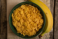 Cereal flakes and banana. Sugary cereal and banana in a rustic arrangement Royalty Free Stock Photos