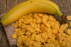 Cereal flakes and banana. Sugary cereal on a wooden background Stock Photo
