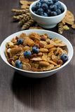 Cereal flakes with blueberries and nuts on wooden table. Vertical, closeup Stock Image