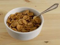 Cereal flakes in bowl. Cereal flakes in bowl and silver spoon on wooden board Stock Image