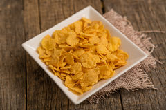 Cereal flakes in a bowl. Sugary cereal on a wooden background Stock Image