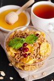 Cereal flakes with fresh berries in a bowl, cup of tea and honey. Vertical Royalty Free Stock Image