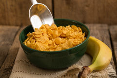 Cereal flakes in a green bowl and banana. Sugary cereal in a rustic arrangement Royalty Free Stock Photo