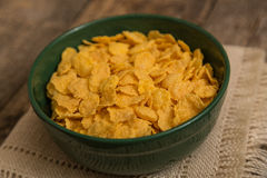 Cereal flakes in a green bowl. Sugary cereal on a wooden background Stock Image