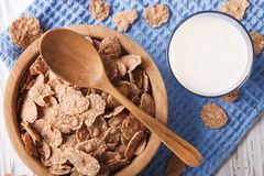 Cereal flakes in a wooden bowl and milk close-up. top view horiz Royalty Free Stock Image