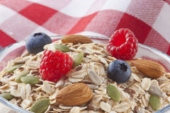 Cereal Food Breakfast Fruit. Closeup detail of a bowl full of muesli breakfast cereal, with oats, almonds, grains and berries with a red checked background Stock Photos