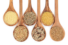 Cereal and Grain Food. Cereal and grain selection of bulgur wheat, buckwheat, couscous, rye grain and brown and wild rice in olive wood spoons on white Royalty Free Stock Photography