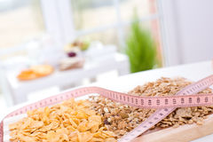 Cereal and measure tape. Diet / Cereal on the board and measure tape Royalty Free Stock Images