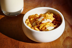 Cereal with milk. Corn flakes and almond cereal against wooden background stock image