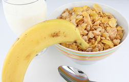 Cereal, Milk and Banana. Breakfast still life with bowl of cereal flakes, glass of milk, banana and spoon stock image