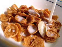 Cereal, Milk Pouring In. Bowl of Almond Cereal, Milk pouring into bowl royalty free stock image