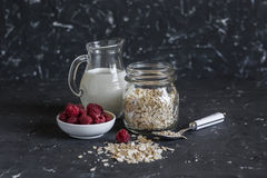 Cereal, milk, raspberries - raw ingredients for cooking a healthy breakfast. On a dark background Royalty Free Stock Photo