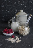 Cereal, milk, raspberries - raw ingredients for cooking a healthy breakfast. On a dark background Royalty Free Stock Image