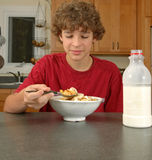 Cereal morning. 12 year-old boy about to have his first spoonful of cereal Royalty Free Stock Photos