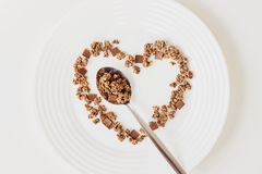 Cereal muesli breakfast and spoon on white background. Healthy eating and lifestyle concept. Cereal muesli breakfast in the shape of a heart and spoon on white royalty free stock photos