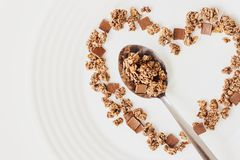 Cereal muesli breakfast and spoon on white background. Healthy eating and lifestyle concept. Cereal muesli breakfast in the shape of a heart and spoon on white royalty free stock images
