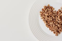 Cereal muesli breakfast on white background. Healthy eating and lifestyle concept. Cereal muesli breakfast in the shape of a heart on white plate background royalty free stock photo