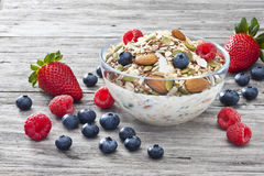Cereal Muesli Granola Berries Breakfast. A bowl of muesli breakfast cereal and milk with berries on a rustic wood background Royalty Free Stock Photo