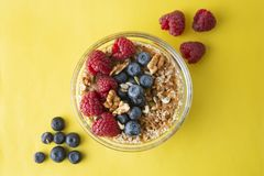 Cereal, muesli and various delicious fruit, berries for breakfast. healthy, energy breakfast, yellow colorful background. To pview royalty free stock image