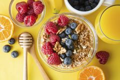 Cereal, muesli and various delicious fruit, berries for breakfast. healthy, energy breakfast, yellow colorful background. To pview royalty free stock photo