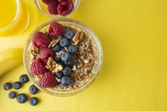 Cereal, muesli and various delicious fruit, berries for breakfast. healthy, energy breakfast, yellow colorful background. To pview royalty free stock images