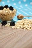 Cereal na tabela, em amoras-pretas e em uma colher do mel Fotografia de Stock