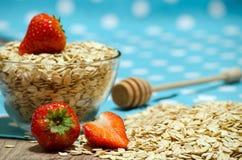 Cereal na tabela, em morangos e em uma colher do mel Imagem de Stock Royalty Free