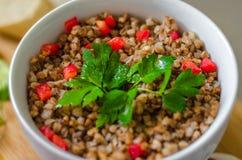 Cereal orgânico, papa de aveia do trigo mourisco com pimenta vermelha doce desbastada Foto de Stock