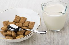 Cereal pillows, teaspoon in white bowl, jug of milk. On wooden table Royalty Free Stock Image