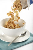 Cereal pouring into bowl. A tabletop view of breakfast cereal flakes being poured from a box into a bowl Royalty Free Stock Photography