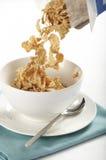 Cereal que vierte en el tazón de fuente Fotografía de archivo libre de regalías