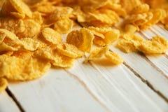 Cereal quebradizo de oro para el desayuno en un fondo de madera blanco imagenes de archivo