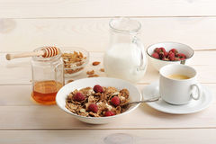 Cereal with raspberries and almonds, milk, honey and coffee heal. Thy Breakfast on wooden background Stock Photos
