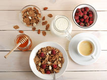 Cereal with raspberries and almonds, milk, honey and coffee heal. Thy Breakfast on wooden background - top view Royalty Free Stock Images
